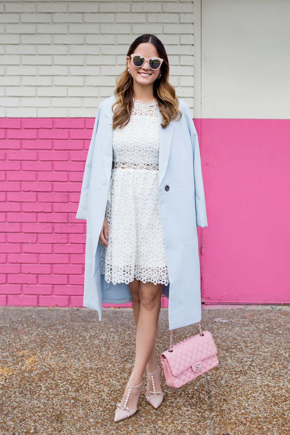 Jennifer Lake Style Charade wearing a white lace bell sleeve dress, long blue coat, Kate Spade Lydia heels, and pink Chanel quilted flap bag at a Chicago pink wall