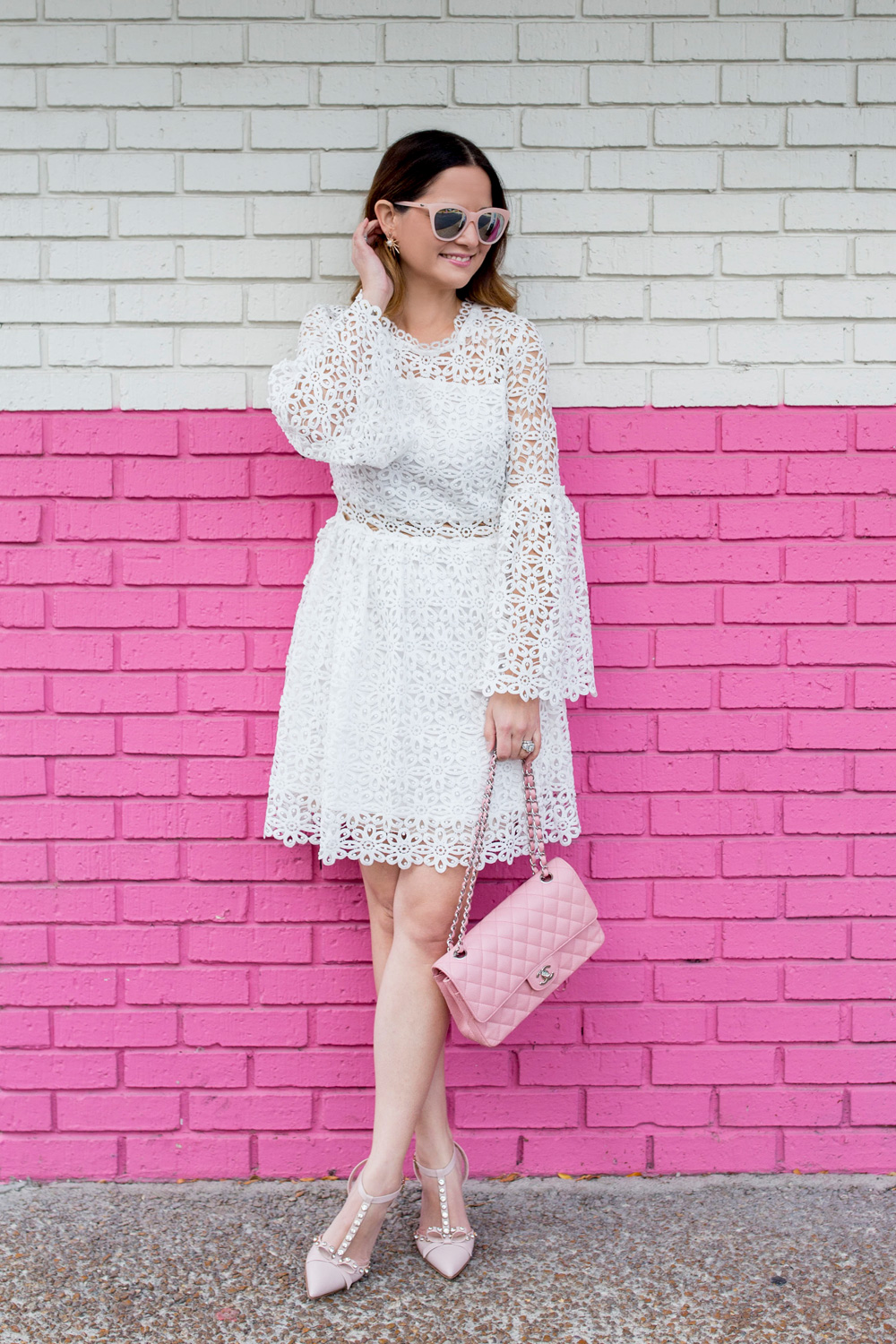 Jennifer Lake Style Charade wearing a white lace bell sleeve dress, Kate Spade Lydia heels, and pink Chanel quilted flap bag pink wall Chicago