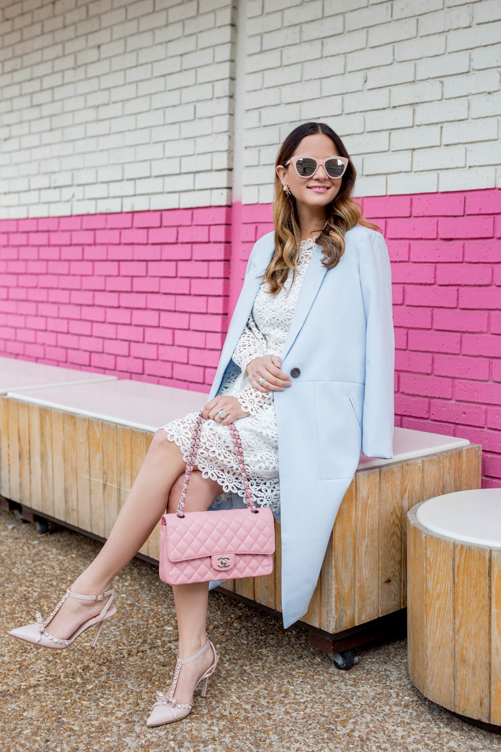 Jennifer Lake Style Charade wearing a white lace bell sleeve dress, long blue coat, Kate Spade Lydia heels, and pink Chanel quilted flap bag pink wall Chicago
