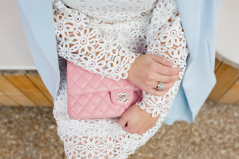Jennifer Lake Style Charade wearing a white lace bell sleeve dress, long blue coat, and pink Chanel quilted flap bag, Cartier love ring