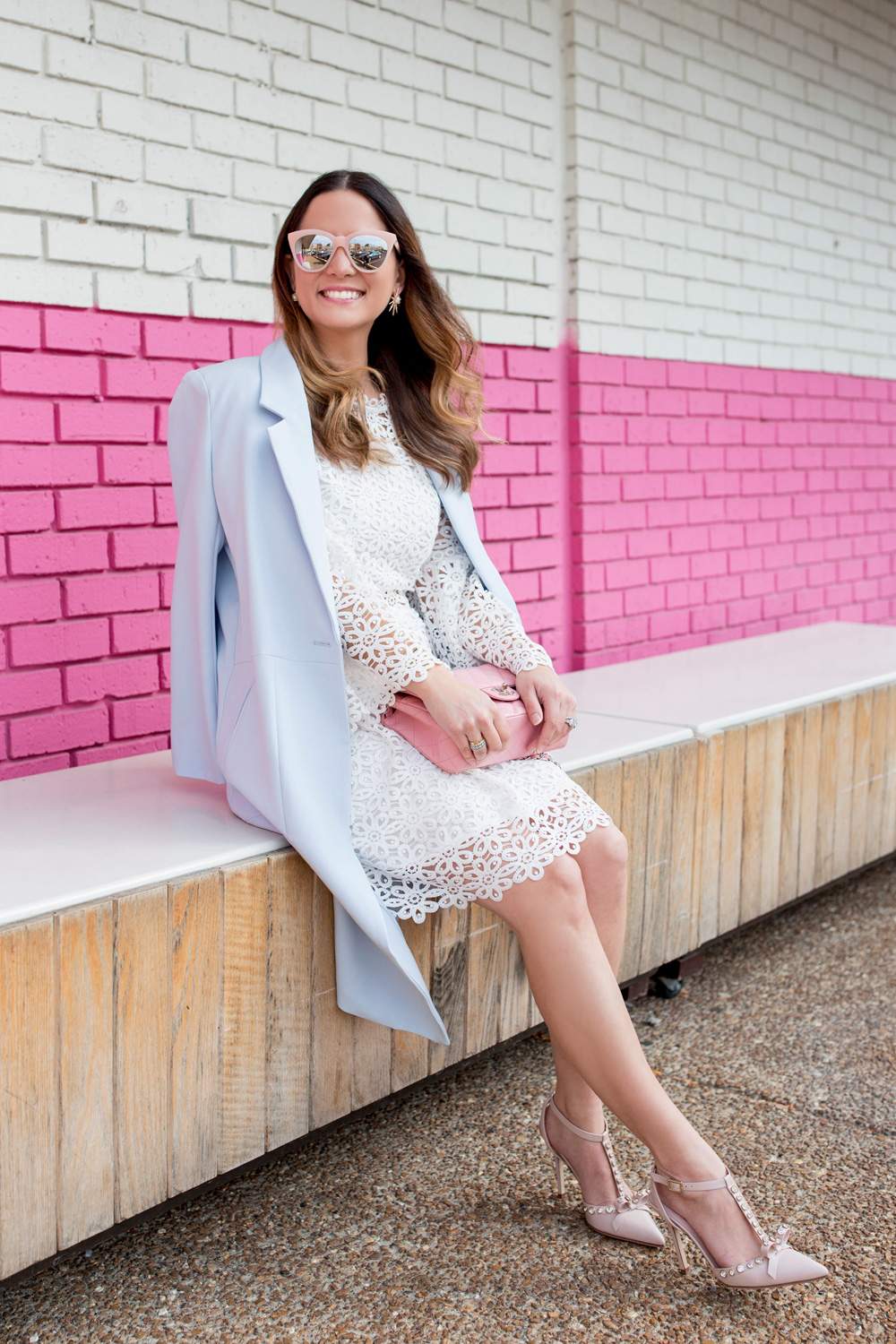 Jennifer Lake Style Charade wearing a white lace bell sleeve dress, long blue coat, Kate Spade Lydia heels, and pink Chanel quilted flap bag pink wall Chicago, Quay pink sunglasses