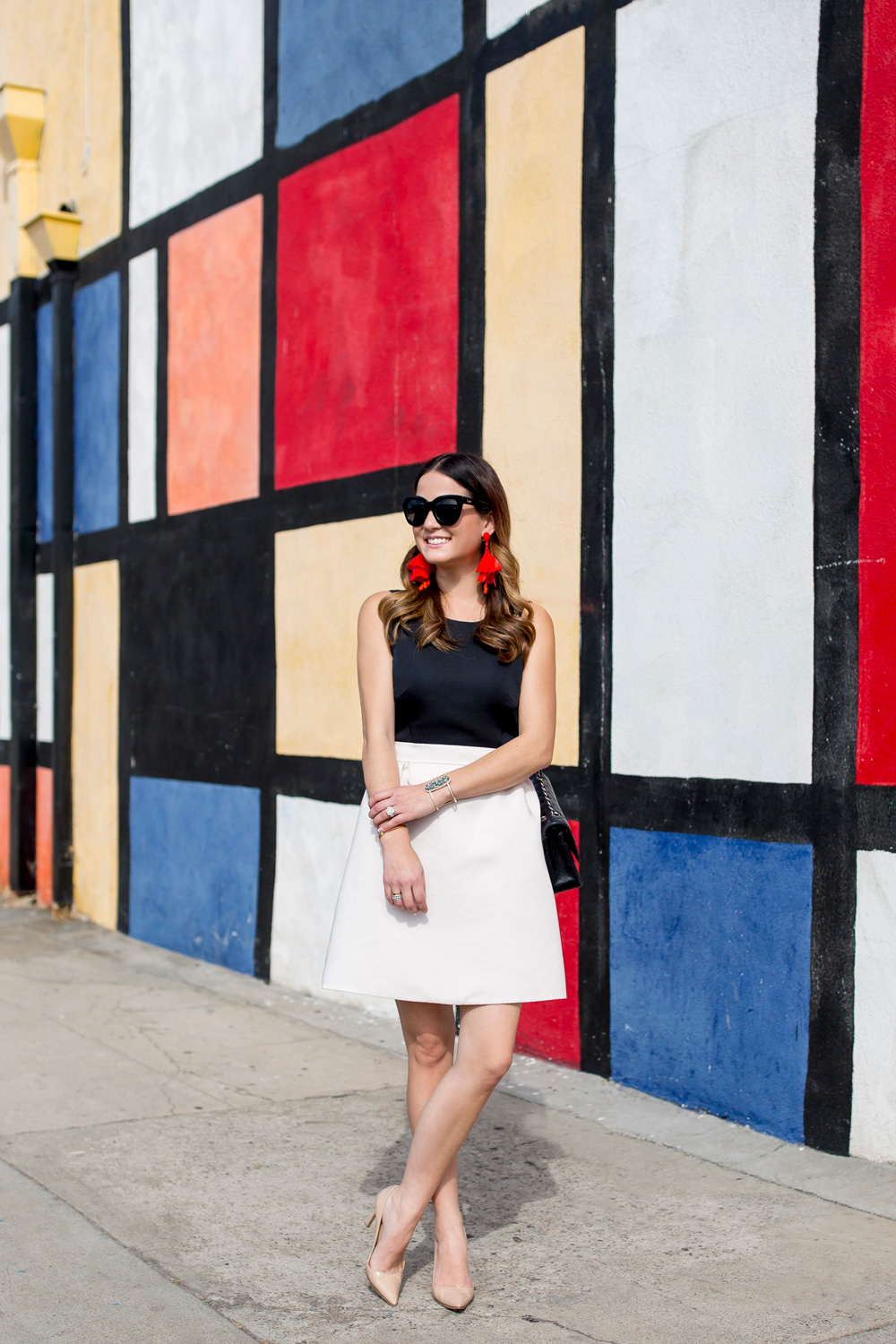 Jennifer Lake Style Charade in a black and white Kate Spade dress and a red Oscar de la Renta floral earrings at a colorful Mondrian wall mural in Los Angeles
