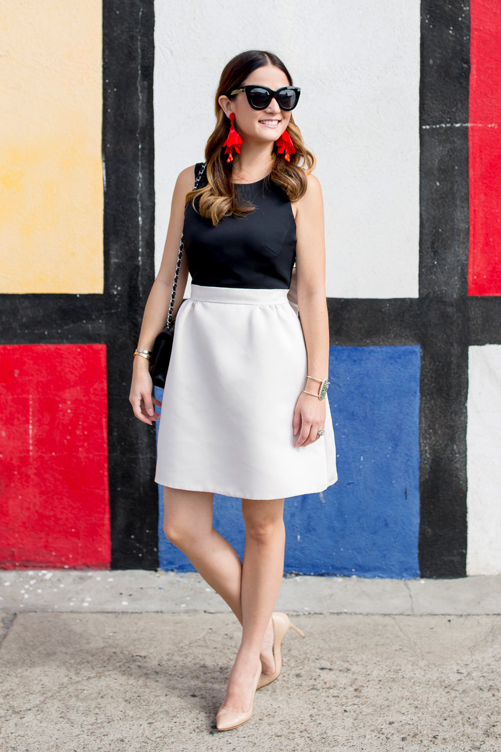 Jennifer Lake Style Charade in a black and white Kate Spade bow dress, red Oscar de la Renta floral earrings, and Manolo Blahnik BB pumps at a Mondrian mural in Los Angeles