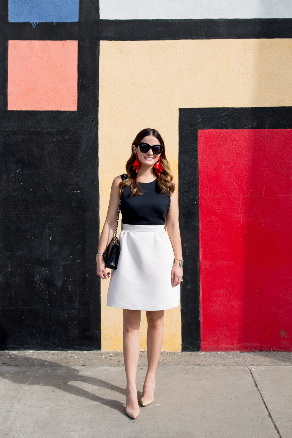 Jennifer Lake Style Charade in a black and white Kate Spade bow dress, red Oscar de la Renta floral earrings, and Chanel quilted flap bag at a Mondrian mural in Los Angeles