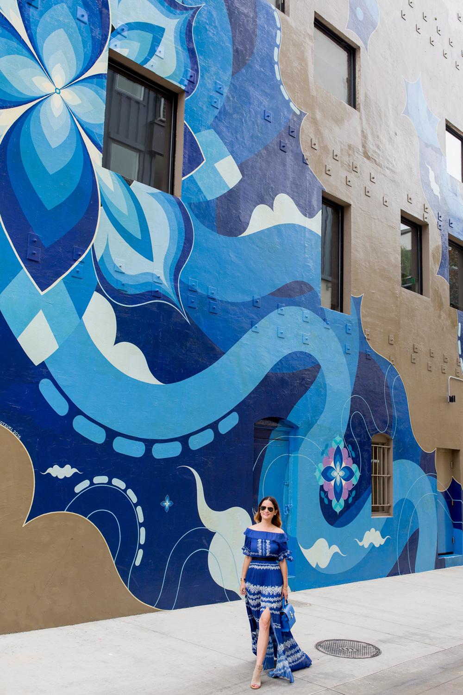 Jennifer Lake Style Charade wearing a blue pleated Self Portrait maxi dress, and blue Henri Bendel bag at a large blue swirl mural wall