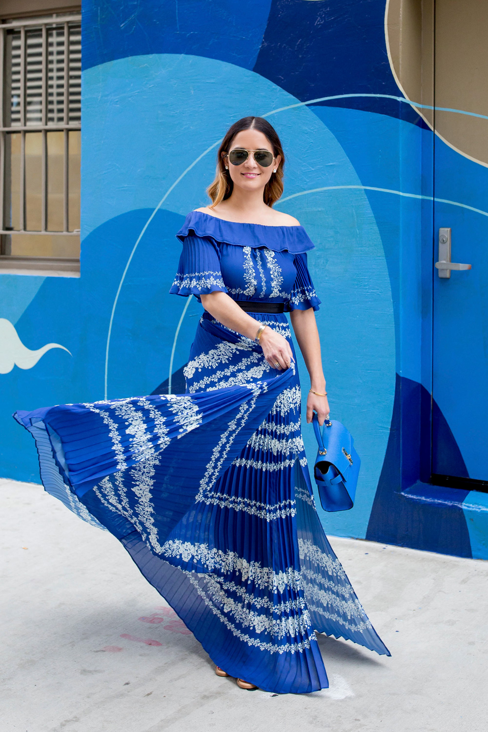 Jennifer Lake Style Charade twirling in a blue pleated Self Portrait maxi dress, and blue Henri Bendel bag at a blue swirl mural wall