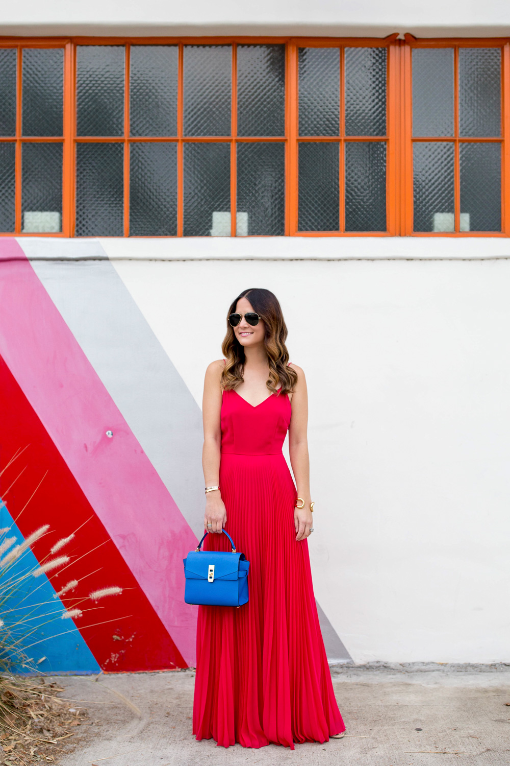 Jennifer Lake Style Charade in an ASOS pink pleated maxi dress, blue Henri Bendel Mini Uptown satchel, at a Free City striped wall in Los Angeles