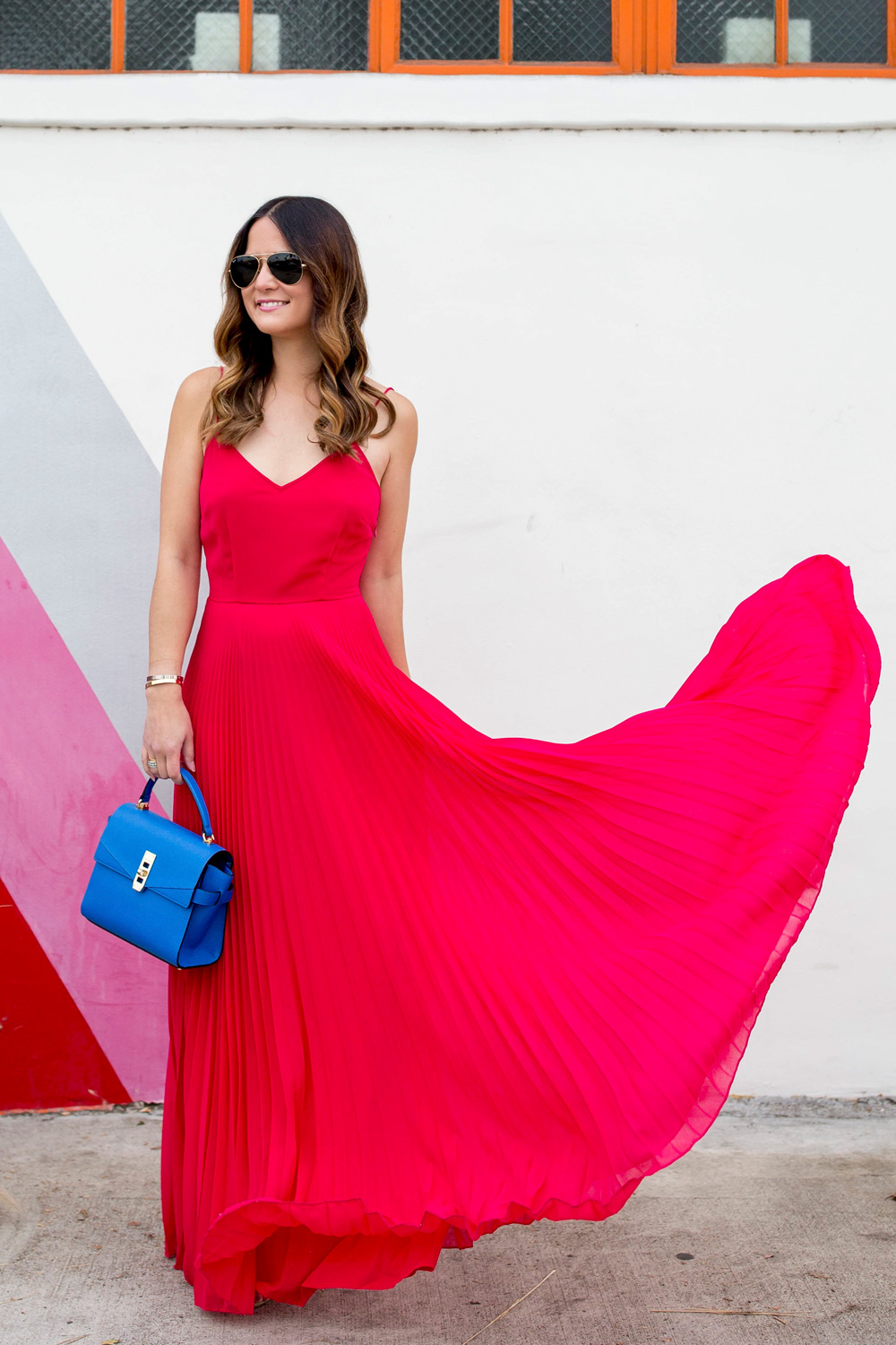Jennifer Lake Style Charade in a flowing ASOS pink pleated maxi dress, blue Henri Bendel Mini Uptown satchel, at a striped wall in Los Angeles