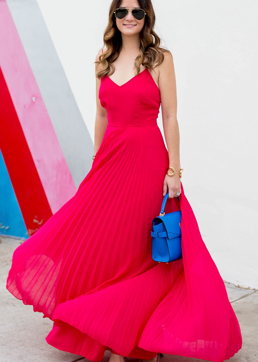 Jennifer Lake Style Charade twirling in an ASOS pink pleated maxi dress, blue Henri Bendel Mini Uptown satchel, at a striped wall in Los Angeles