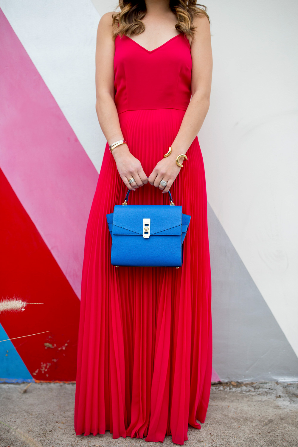 Jennifer Lake Style Charade in an ASOS pink maxi dress, blue Henri Bendel Mini Uptown satchel, and Giles and Brother Cortina cuff at a striped wall in Los Angeles