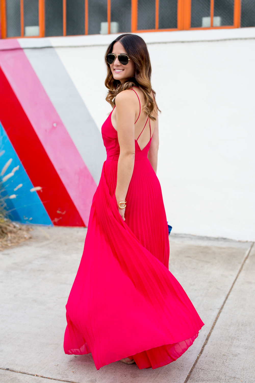 Jennifer Lake Style Charade walking in an ASOS pink pleated maxi dress, blue Henri Bendel Mini Uptown satchel, at a striped wall in Los Angeles