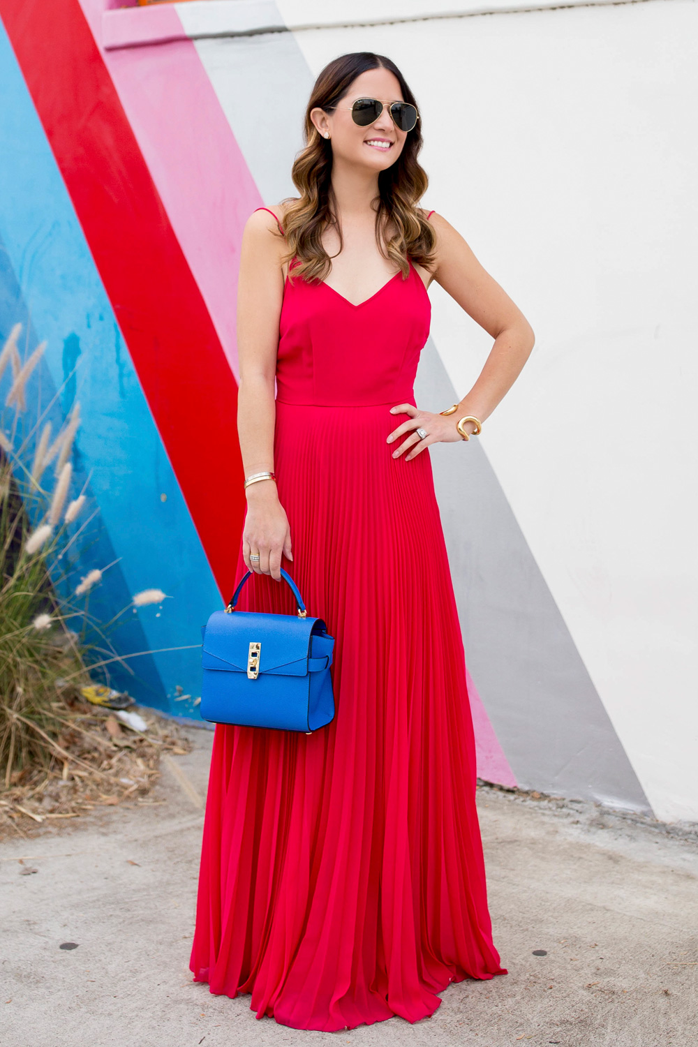 Jennifer Lake Style Charade in an ASOS bright pink pleated maxi dress, blue Henri Bendel Mini Uptown satchel, at a Los Angeles striped wall