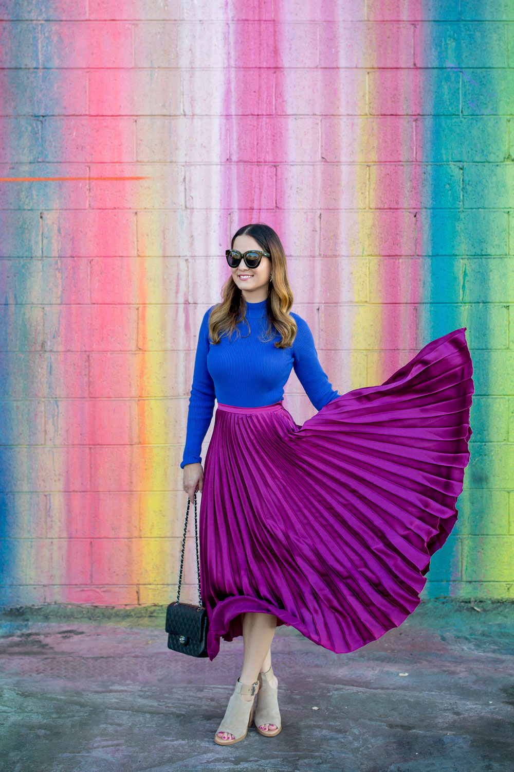 Jennifer Lake Style Charade flicking a ASOS purple pleated midi skirt, cobalt blue sweater bodysuit and Chanel quilted flap bag at a dripping paint wall in Los Angeles