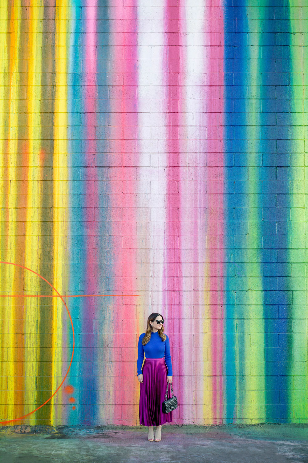 Jennifer Lake Style Charade standing in an ASOS purple pleated midi skirt, cobalt blue sweater bodysuit and Chanel quilted flap bag at a dripping paint wall in Los Angeles