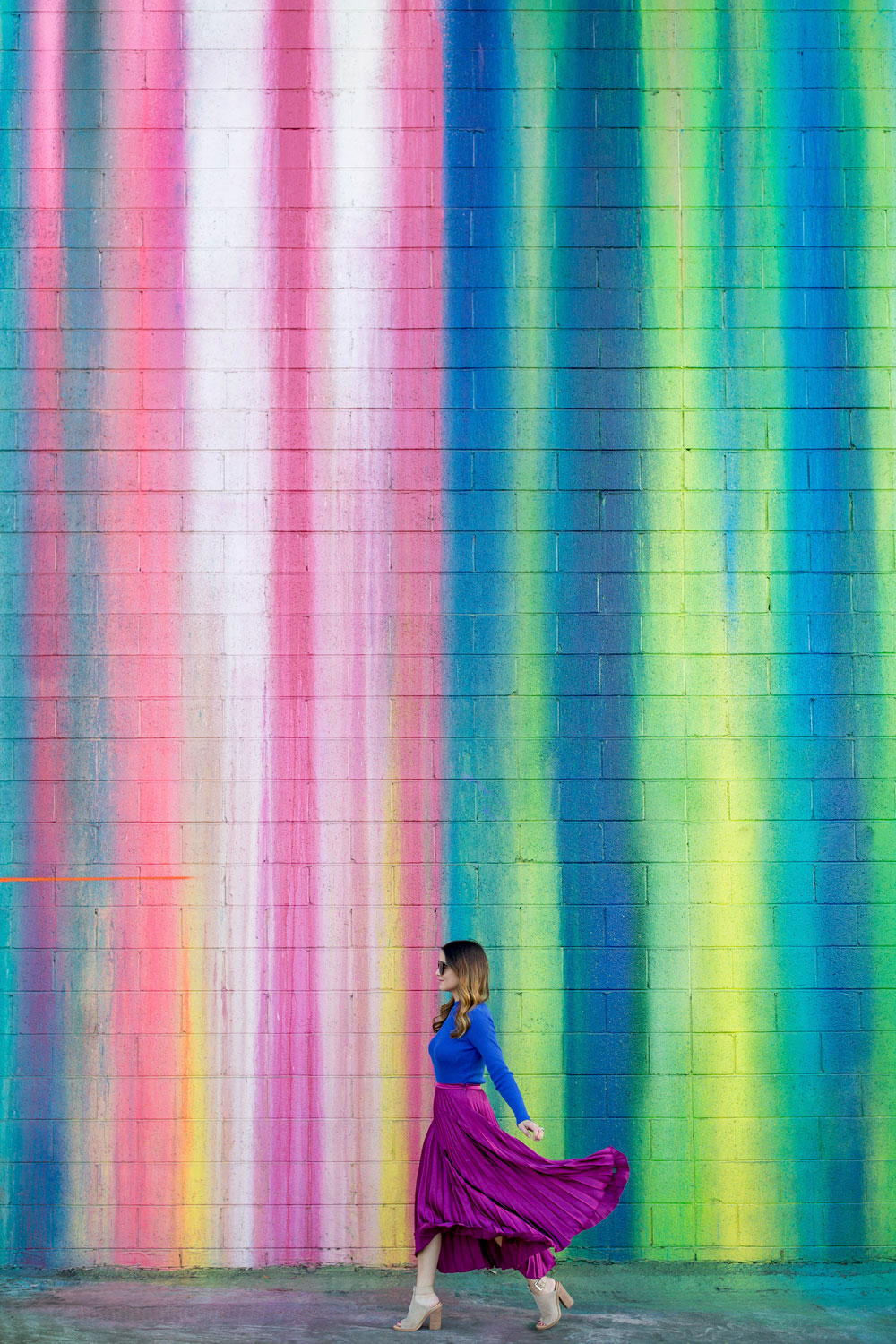 Jennifer Lake Style Charade walking in an ASOS purple pleated midi skirt, cobalt blue sweater bodysuit and Chanel quilted flap bag at a dripping paint wall in Los Angeles