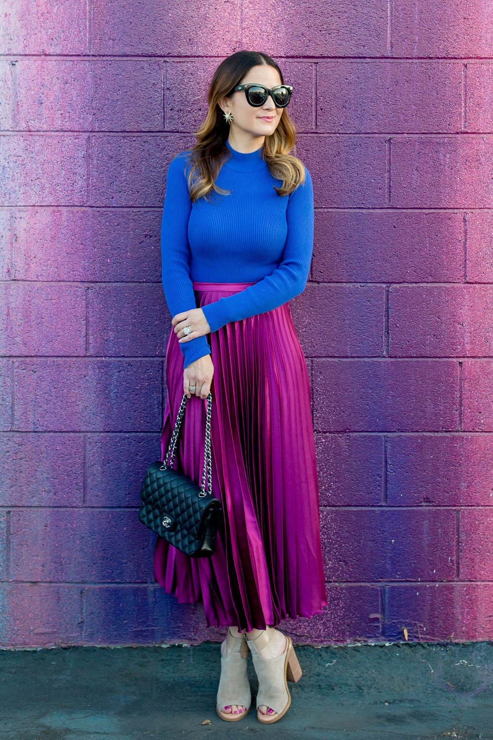 Jennifer Lake Style Charade leaning in an ASOS purple pleated midi skirt, cobalt blue sweater bodysuit and Chanel quilted flap bag at a dripping paint wall in Los Angeles