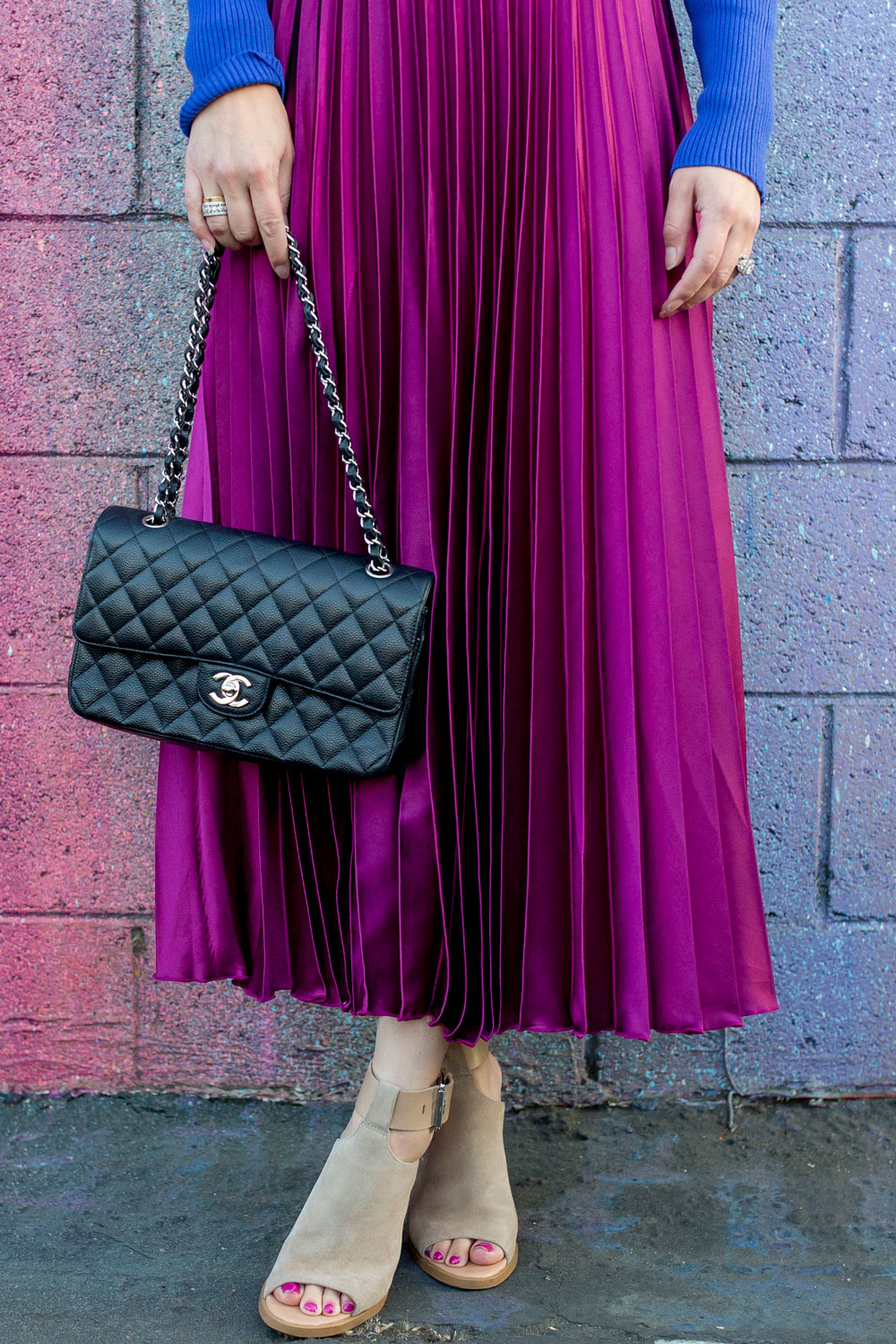 Jennifer Lake Style Charade in an ASOS purple pleated midi skirt, cobalt blue sweater bodysuit and Chanel quilted flap bag at a dripping paint wall in Los Angeles