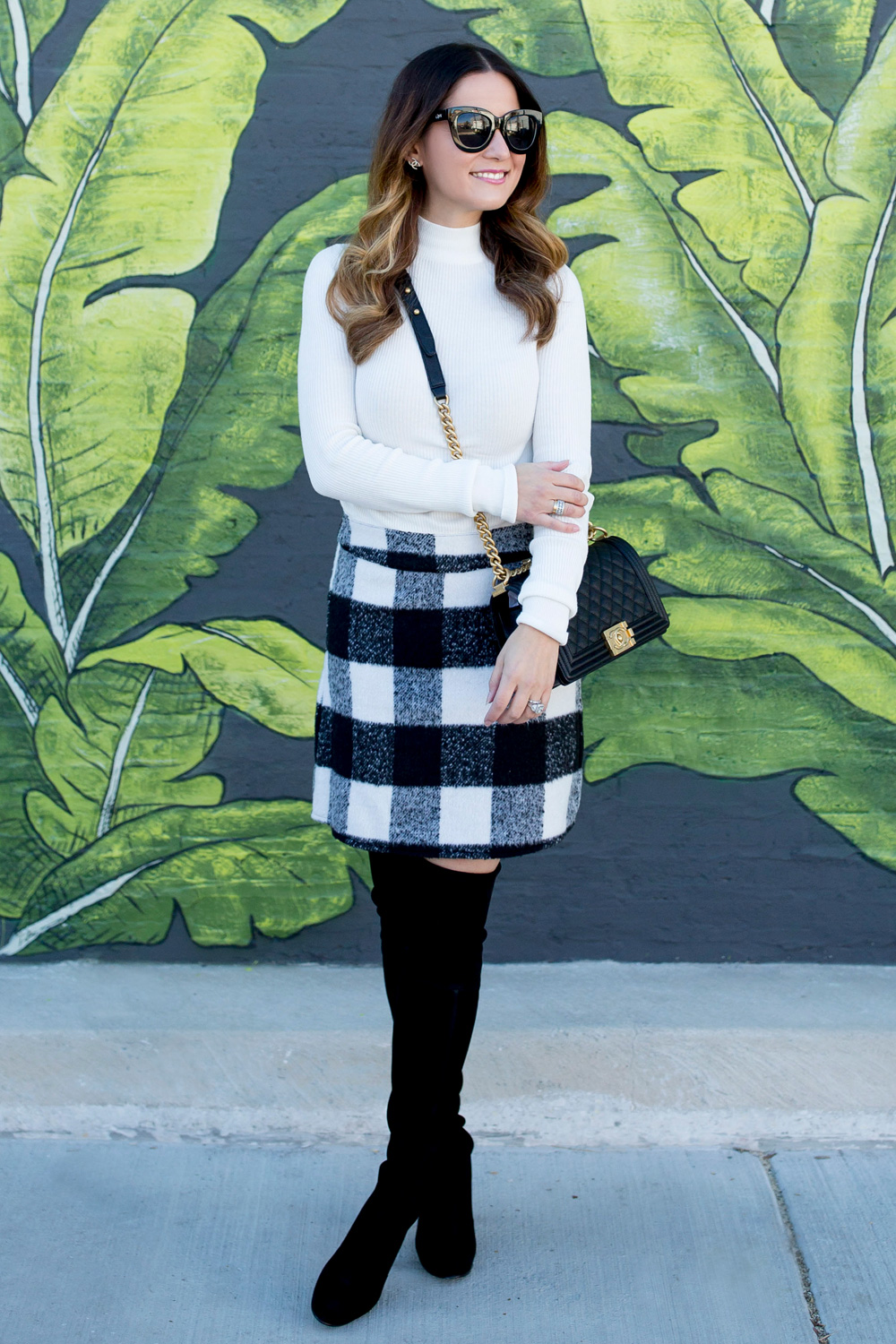 Jennifer Lake Style Charade in an ASOS black white check skirt, Chanel Boy Bag, and Stuart Weitzman Highland boots at a Chicago palm leaf mural