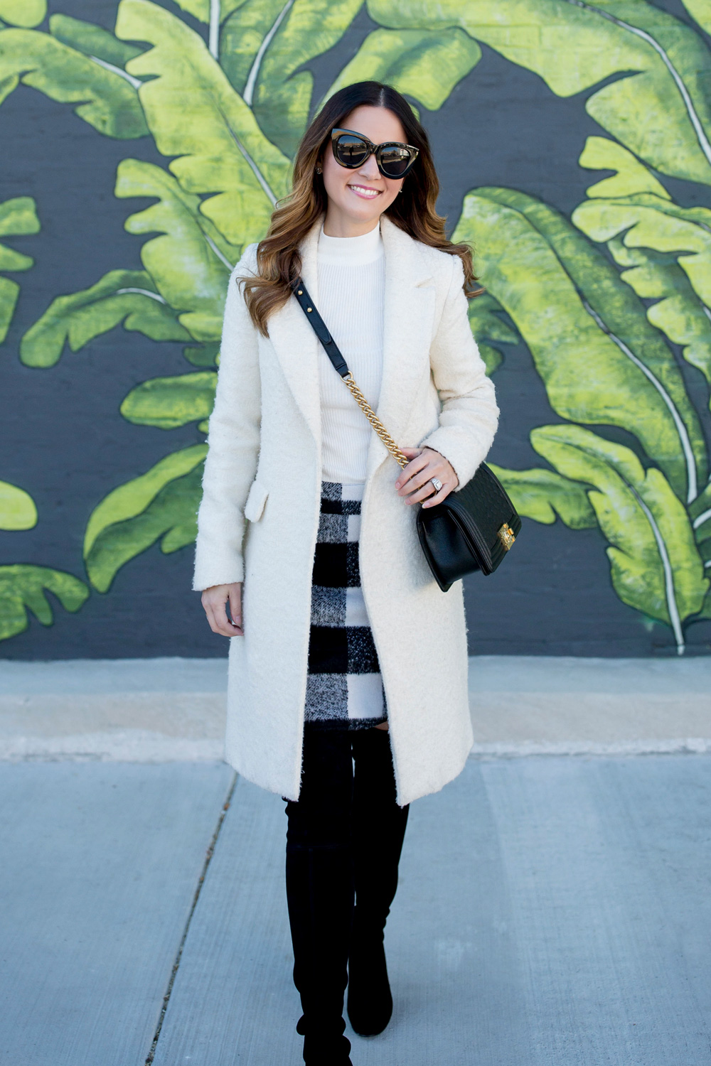 Jennifer Lake Style Charade in an ASOS black white check skirt, ivory coat, Chanel Boy Bag, and Stuart Weitzman Highland boots at a Chicago palm leaf mural