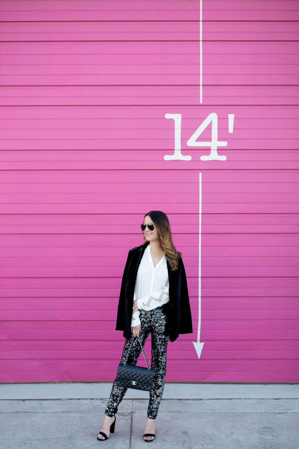 Jennifer Lake Style Charade in Express sequin leggings, black velvet blazer, ivory lace top, and a quilted Chanel flap bag in front of a Chicago pink wall