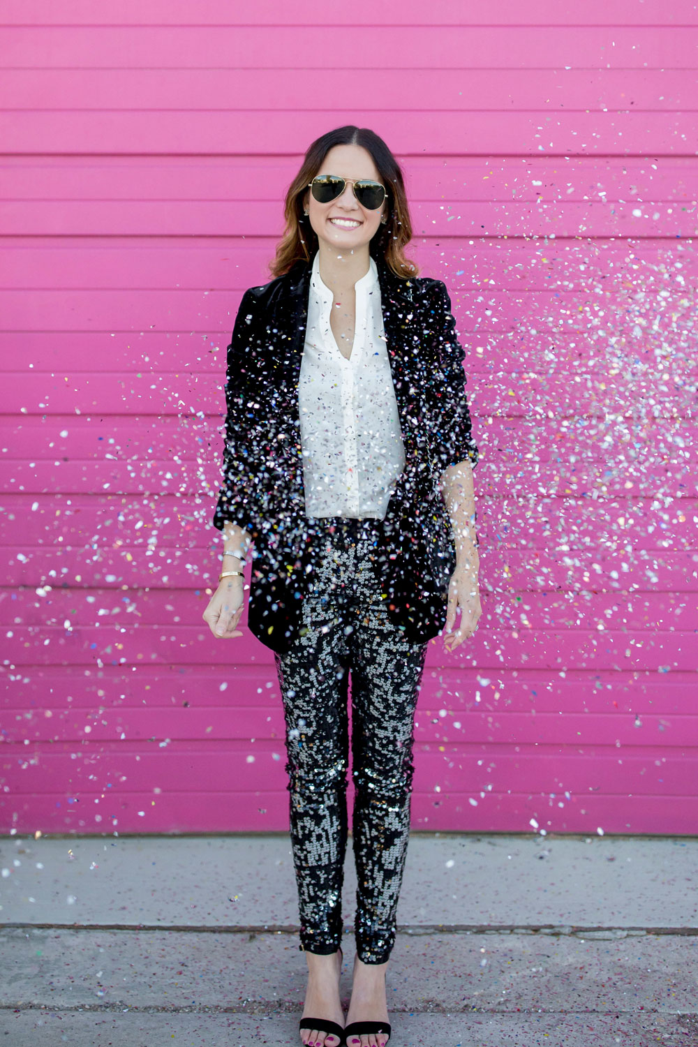 Jennifer Lake Style Charade throwing confetti in Express sequin leggings, black velvet blazer, ivory lace top, and a quilted Chanel flap bag in front of a Chicago pink wall
