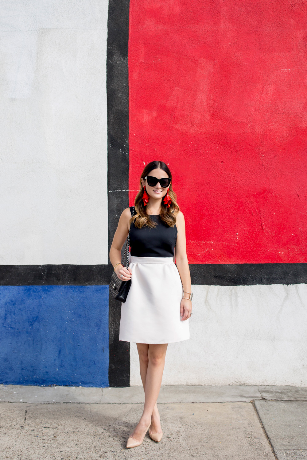 Jennifer Lake Style Charade in a black and white Kate Spade bow dress and a red Oscar de la Renta floral earrings at a colorful Mondrian wall mural in Los Angeles