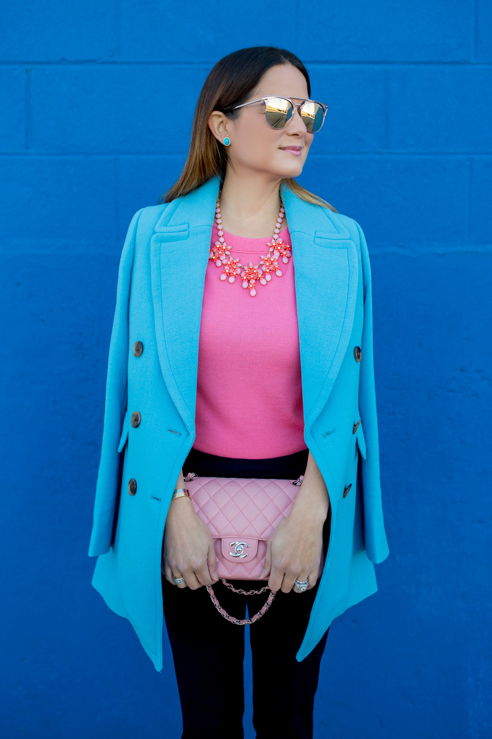 Jennifer Lake Style Charade in J Crew Nordstrom blue coat, pink cashmere sweater, pink Chanel quilted flap bag, and Steve Madden Carrson sandals at a blue wall in Chicago