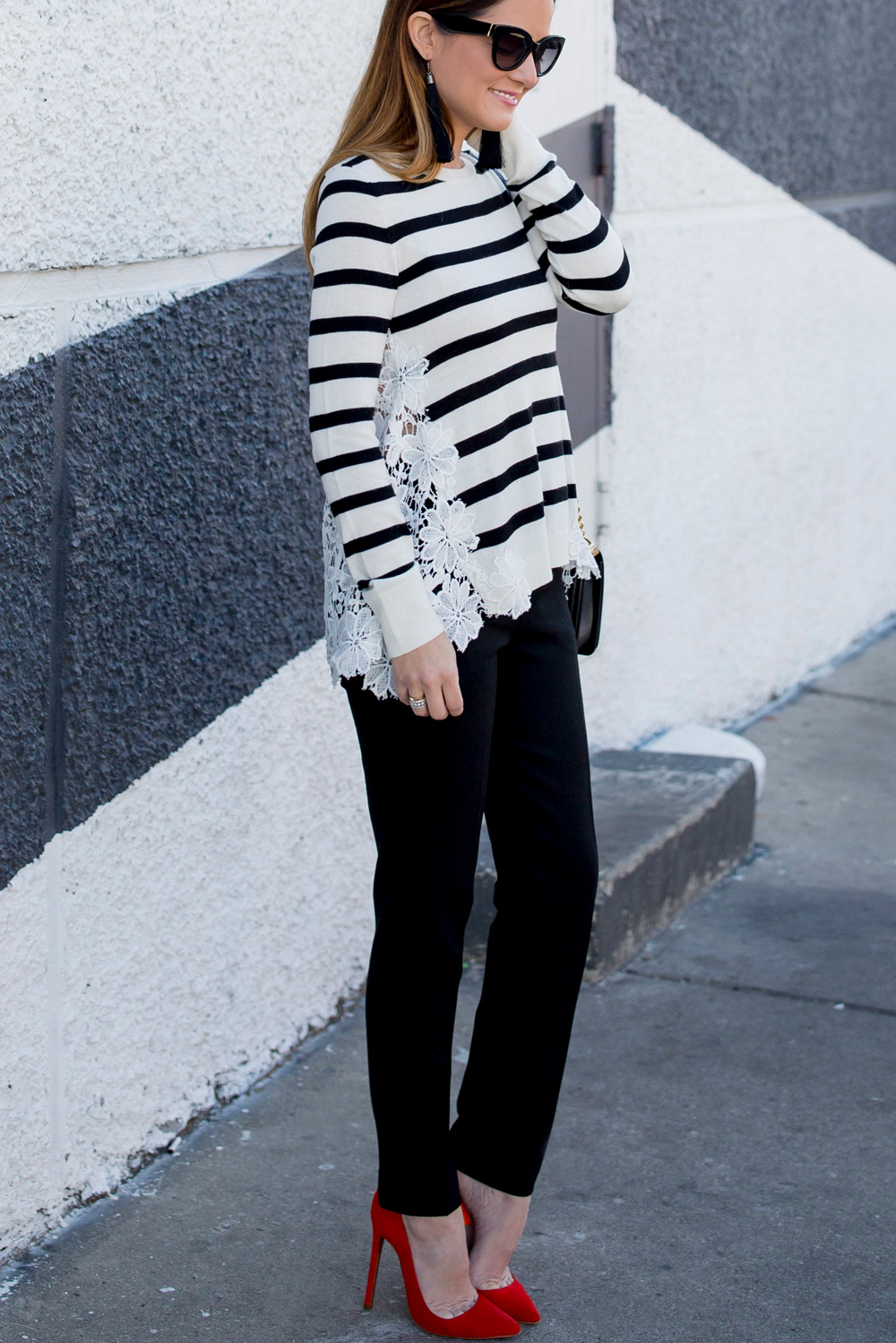 Jennifer Lake Style Charade in a black and white stripe sweater with lace detail, black tassel earrings, and red pumps at a black and white wall in Chicago