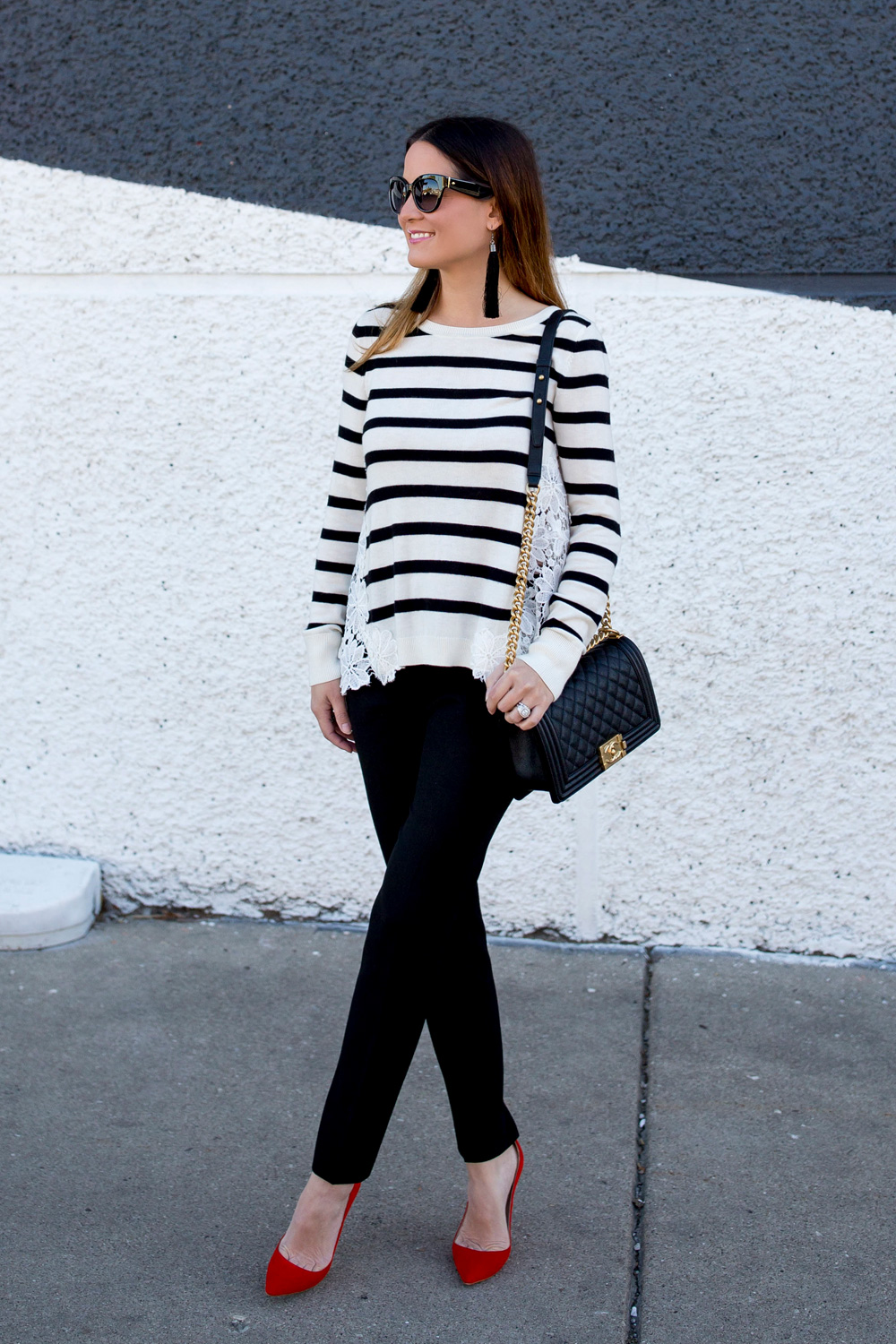 Jennifer Lake Style Charade in a black and white stripe sweater with lace detail, a black and gold Chanel Boy Bag and red pumps at a black and white wall in Chicago