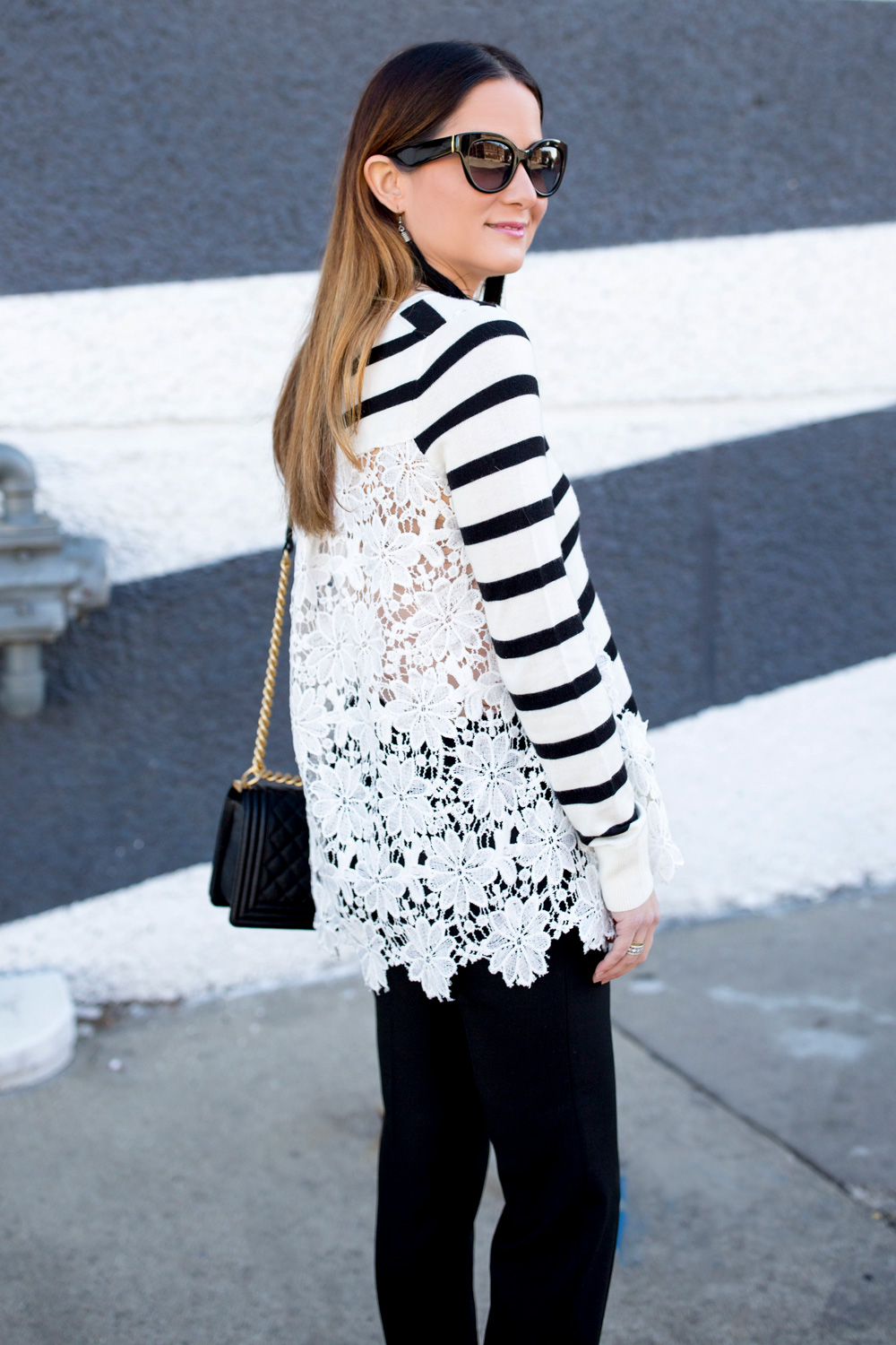 Jennifer Lake Style Charade in a black and white stripe sweater with lace detail, black tassel earrings, and oversized sunglasses in Chicago
