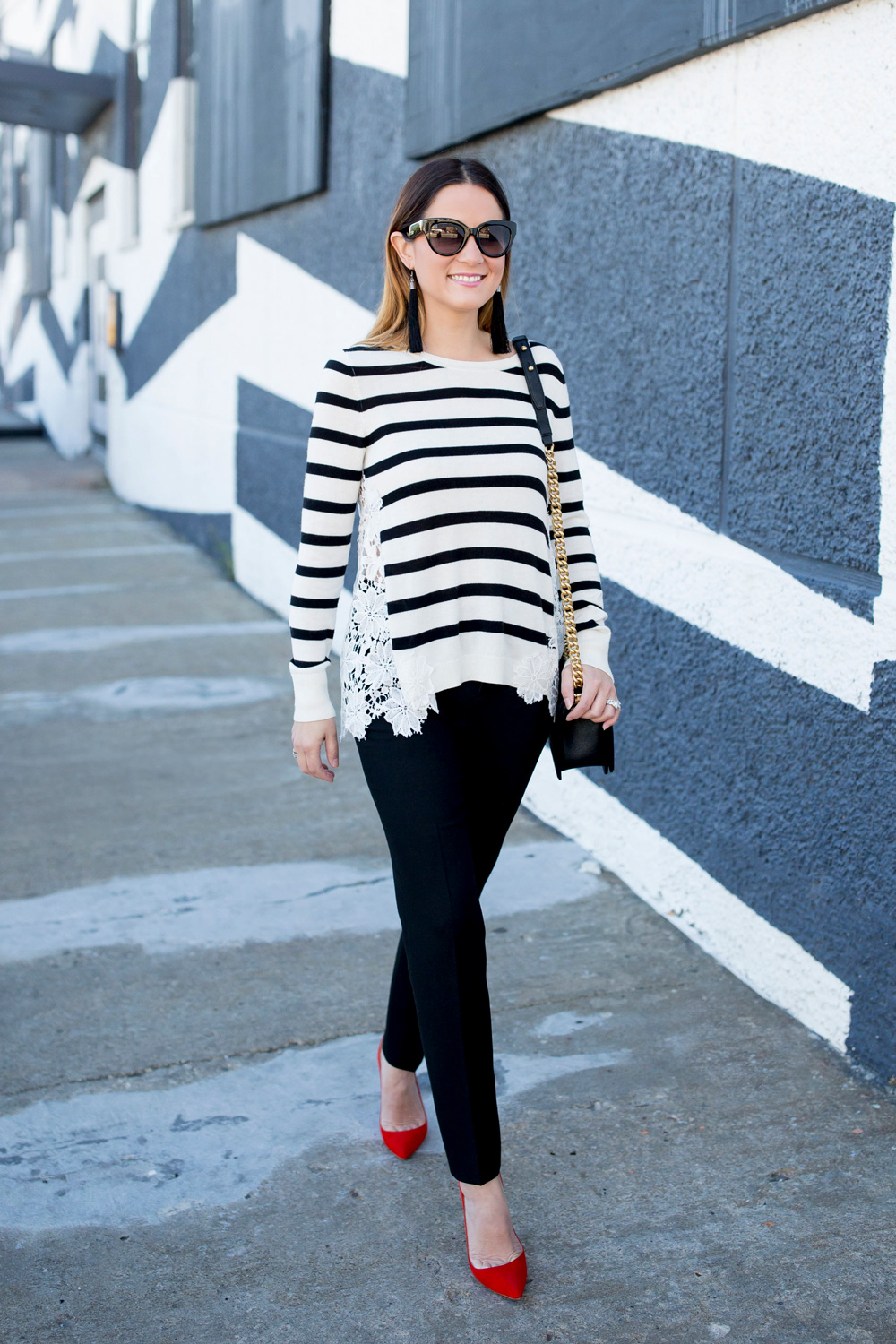 Jennifer Lake Style Charade in a black and white stripe sweater with lace detail, a Chanel Boy Bag, and red pumps at a black and white wall in Chicago